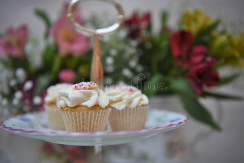Nachmittagstee mit einer Platte von Minikleinen kuchen und von frischen Blumen stockfotos