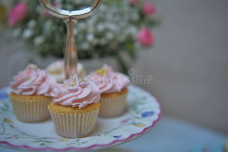 Nachmittagstee mit einer Platte von Minikleinen kuchen und von frischen Blumen stockfoto
