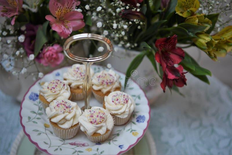 Nachmittagstee mit einer Platte von Minikleinen kuchen und von frischen Blumen lizenzfreies stockfoto
