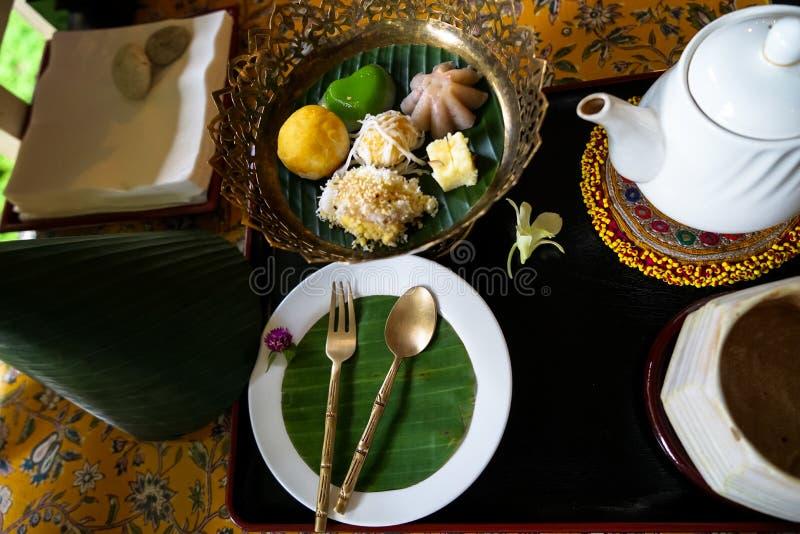 Nachmittagsteezeitsatz des thailändischen traditionellen Nachtischs mit Bananenblatt- und -blumendekoration auf Blumenmustertisch stockbild