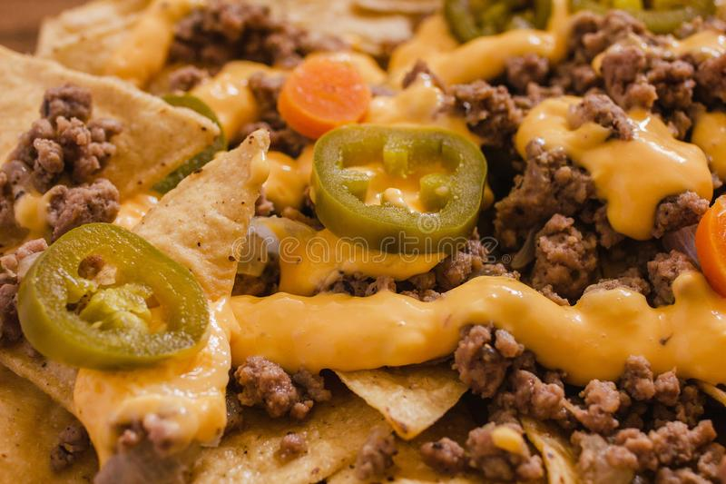 Nacho chips corn garnished with ground beef, melted cheese, jalapenos peppers, mexican spicy food in mexico royalty free stock photography
