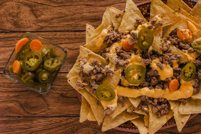 Nacho chips corn garnished with ground beef, melted cheese, jalapenos peppers mexican spicy food in mexico stock image