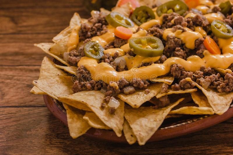 Nacho chips corn garnished with ground beef, melted cheese, jalapeño peppers, mexican spicy food in mexico. Nacho chips corn garnished with ground beef, melted stock images