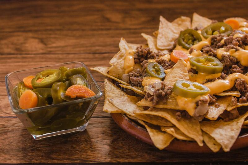 Nacho chips corn garnished with ground beef, melted cheese, jalapeños peppers, mexican spicy food in mexico stock image