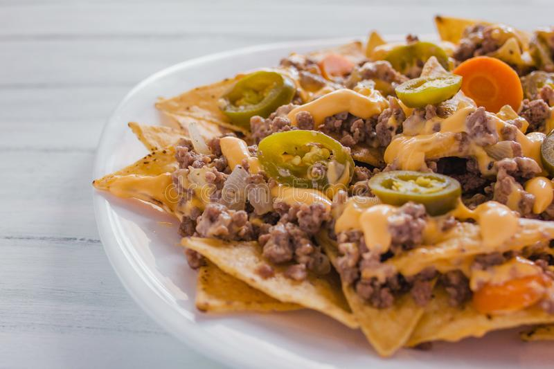 Nacho chips corn garnished with ground beef, melted cheese, jalapeños peppers, mexican spicy food in mexico. Nacho chips corn garnished with ground beef royalty free stock image