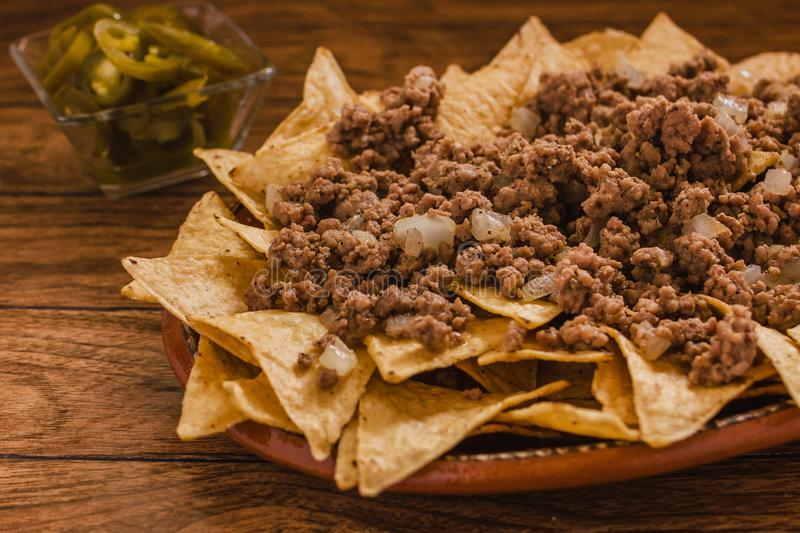 Nacho chips corn garnished with ground beef, melted cheese, jalapeno peppers in plate on wooden table mexican spicy food in mexico royalty free stock photos