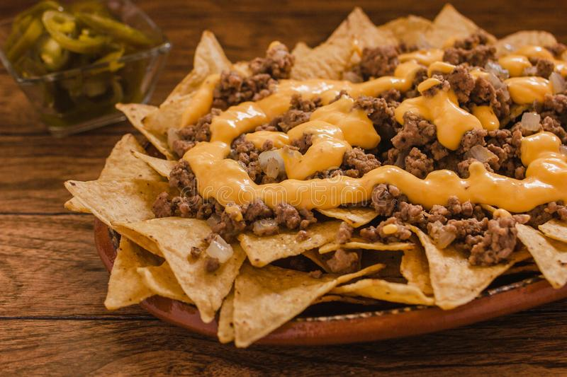 Nacho chips corn with ground beef, melted cheese, jalapeños in plate on wooden table mexican spicy food in mexico royalty free stock image