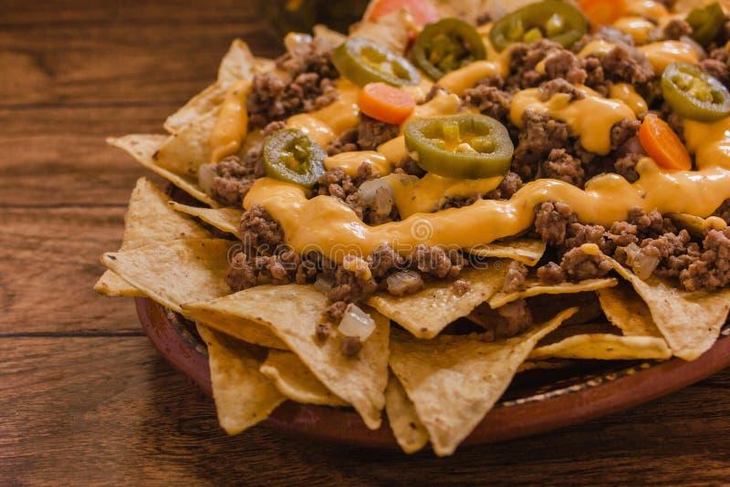 Nacho schneidet den Mais in Stücke, der mit Rinderhackfleisch, geschmolzener Käse, jalapeño Pfeffer, mexikanisches würziges Lebe stockbilder