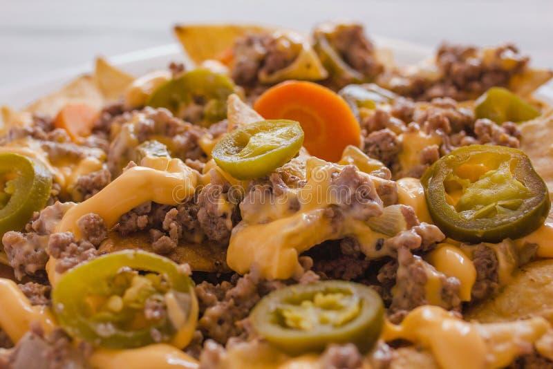 Nachochiper konserverar garnerat med jordnötkött, smältt ost, mexikansk kryddig mat för jalapeñospeppar i Mexiko arkivbild