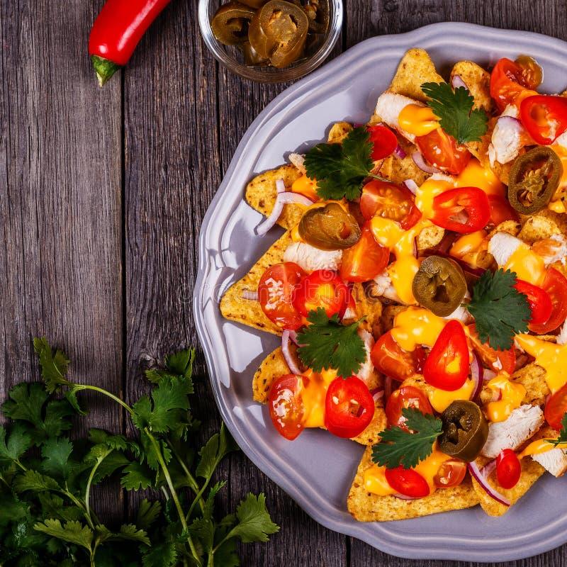 Nachos с расплавленными соусом сыра, jalapeno, цыпленком и овощем стоковые фото