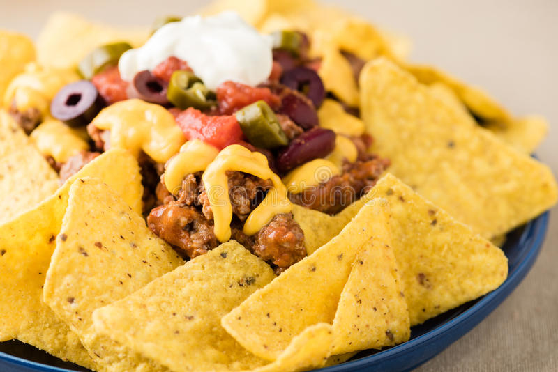 Nachos with beef, jalapeno peppers, olives, tomato, beans, cheese and sour cream stock photo