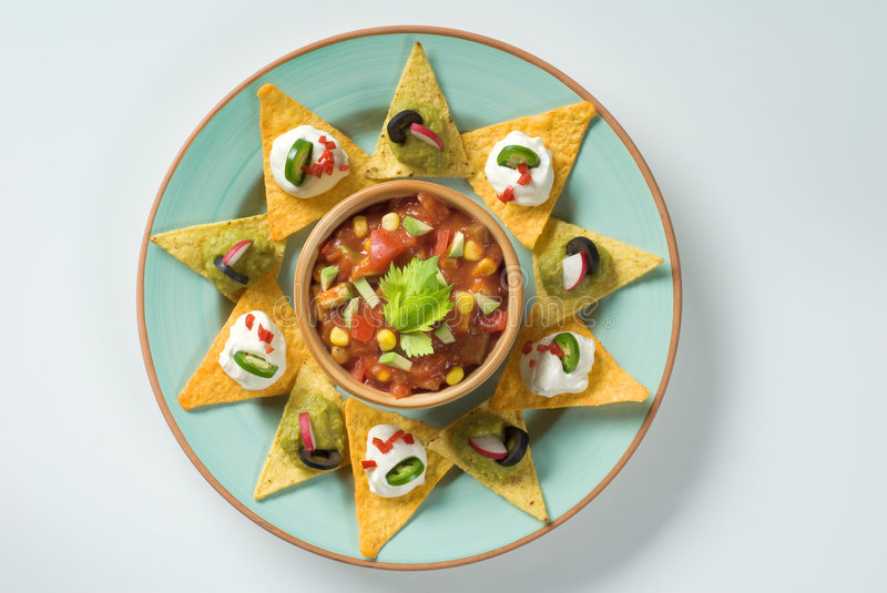 Nachos and a bowl of salsa. Nachos topped with dipping sauces around a bowl of salsa stock image