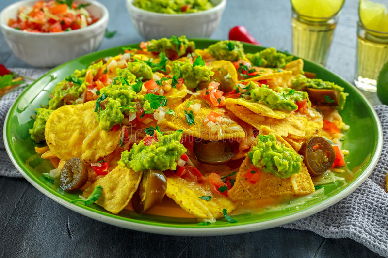 Nachos with cheese, jalapeno peppers, red onion, parsley, tomato, salsa, guacamole sauce and tequila on green plate. royalty free stock images