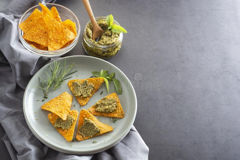 Nachos chips or corn mexican chips with guacamole, pesto pasta healthy food snack, copy space stock images