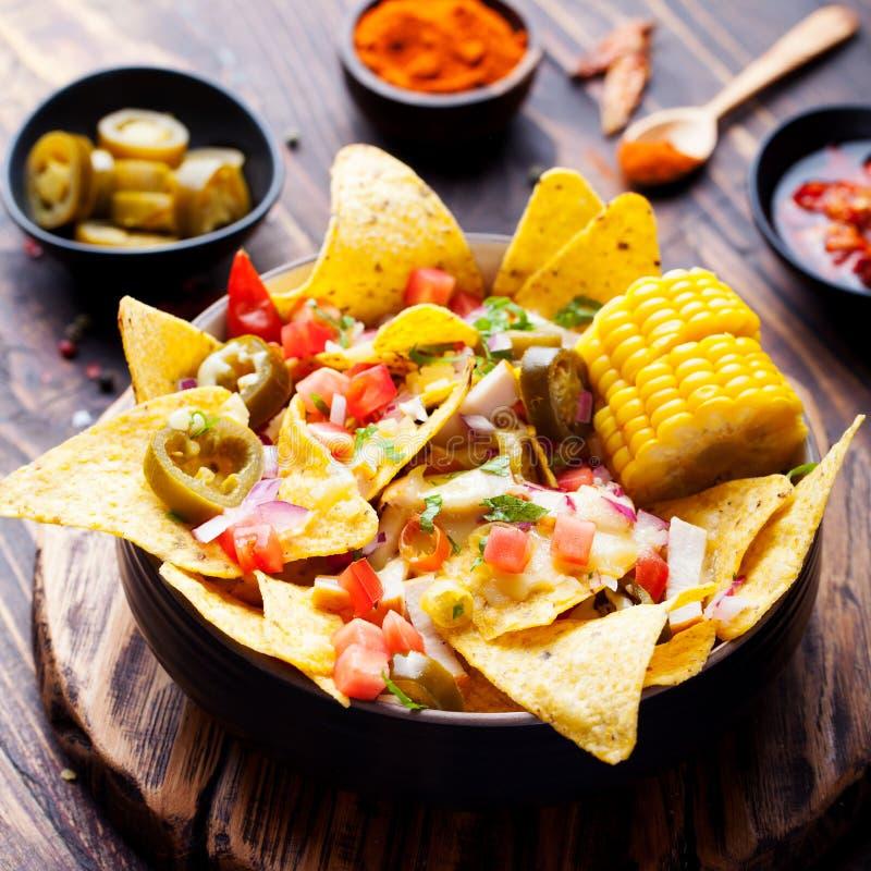Nachos da tortilha, molho de queijo, galinha, jalapeno, tomate, salsa, espigas de milho foto de stock royalty free
