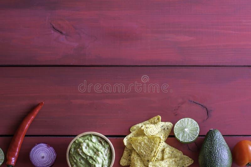Nachos de guacamole et de pommes chips Fond rouge Cuisine mexicaine images stock