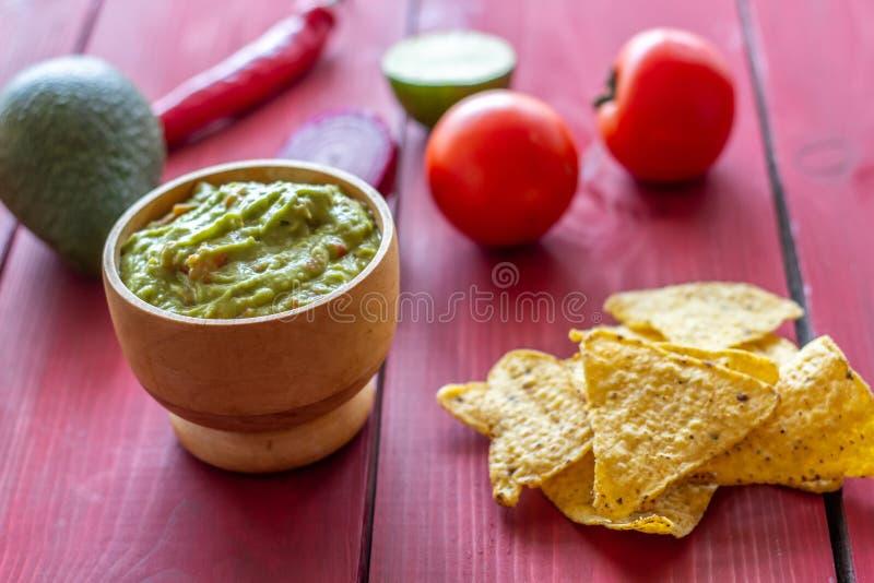 Nachos do Guacamole e das microplaquetas Fundo vermelho Culin?ria mexicana imagens de stock royalty free