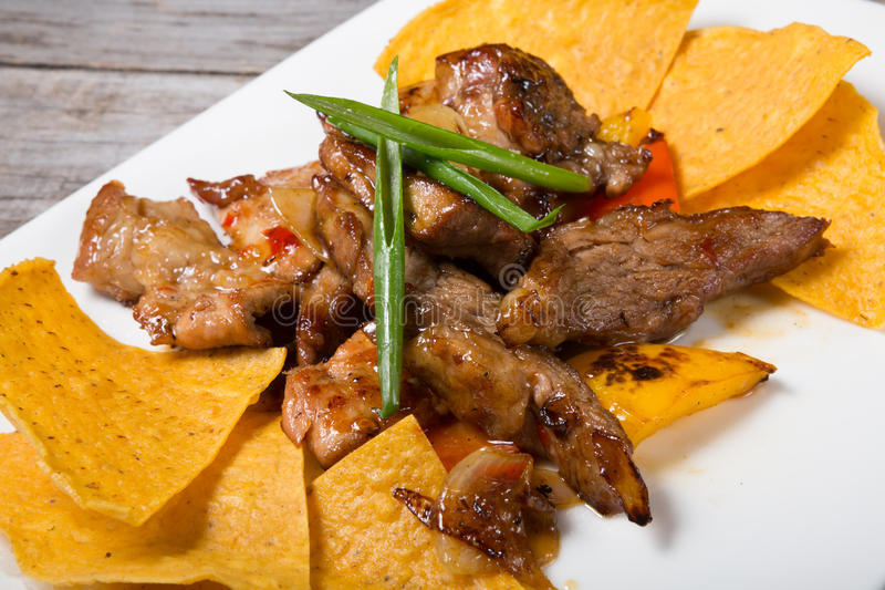 Nachos with fried meat royalty free stock images
