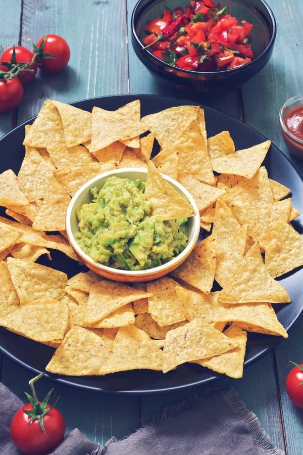 nachos havrechiper med guacamolesås och salsa Latin - amerikansk mat Lantlig grön bakgrund tonat foto fotografering för bildbyråer