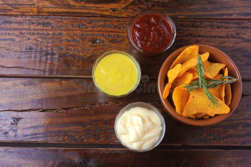 Nachos konserverar chiper som förläggas i keramisk bunke på trätabellen bredvid blandade såser kopiera avstånd arkivfoton