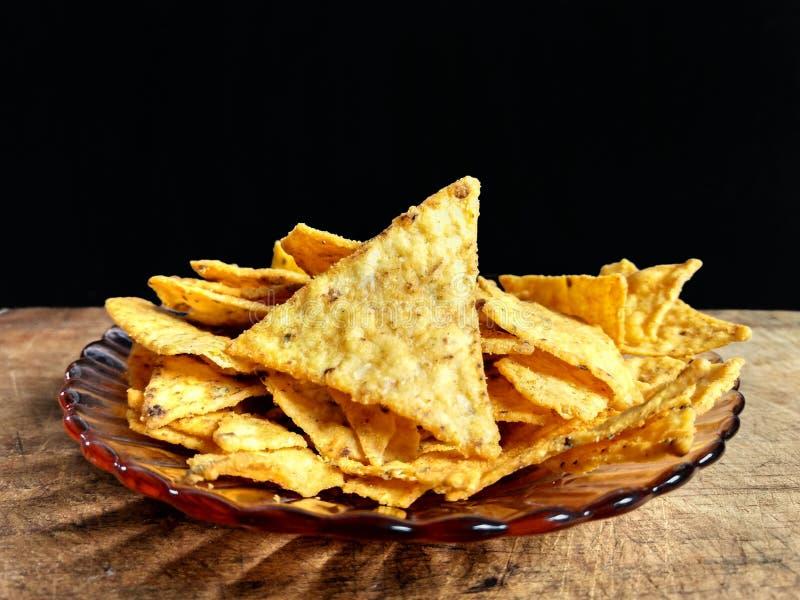 Nachos med ost på träskivor med svart bakgrund royaltyfria bilder
