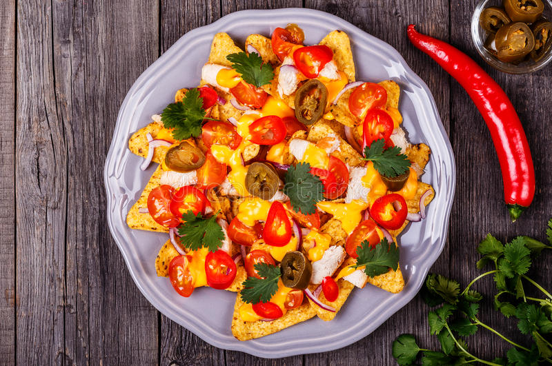 Nachos with melted cheese sauce, jalapeno, chicken and vegetable. S on dark wooden background royalty free stock image