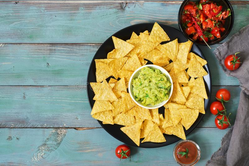 Nachos. Mexican food. Corn chips with sauce of salsa and guacamole on a green blue rustic background. Top view. Nachos. Mexican food. Corn chips with sauce of royalty free stock photo