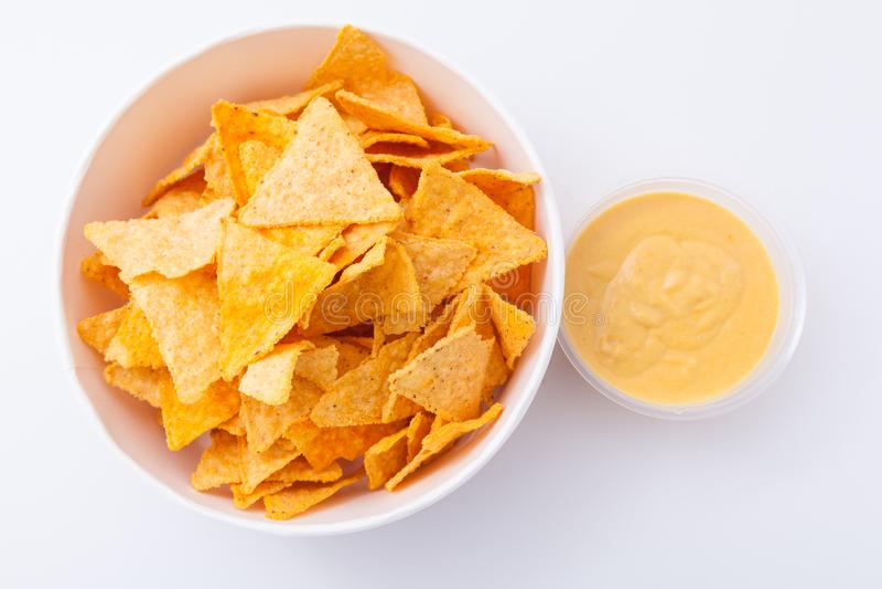 Nachos mexicanos com molho de queijo cremoso Petisco triangular salgado delicioso dos nachos das microplaquetas de milho para o p fotos de stock