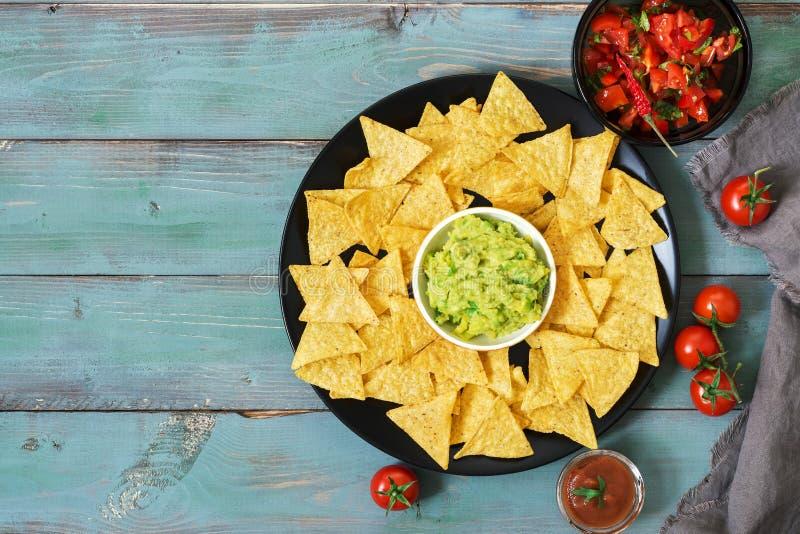 nachos Mexicansk mat Havrechiper med sås av salsa och guacamole på gör grön blå lantlig bakgrund Top beskådar royaltyfri foto