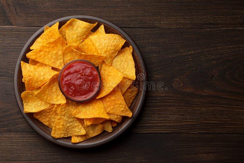 Nachos ou tortilla mexicains de casse-croûte dans le plat d'argile avec de la sauce à immersion sur le fond en bois rustique image libre de droits