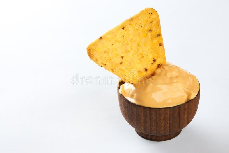 Nachos que sumergen en el cuenco de madera con la salsa de queso cremosa foto de archivo libre de regalías