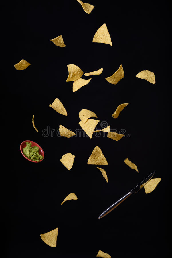 Nachos tortilla corn chips with fresh guacamole sauce flying, black background. stock images