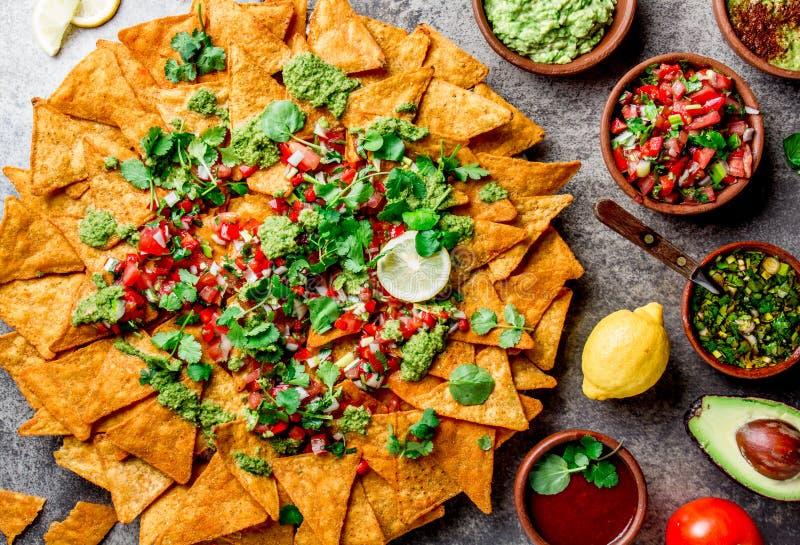 nachos Totopos med såser Mexicanskt matbegrepp Gula havretotopos gå i flisor med olika såssalsor - picodel arkivfoton
