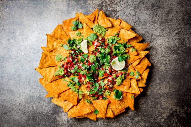 Nachos Totopos met sausen Mexicaans voedselconcept De gele spaanders van graantotopos met verschillende sausensalsas - pico del stock fotografie