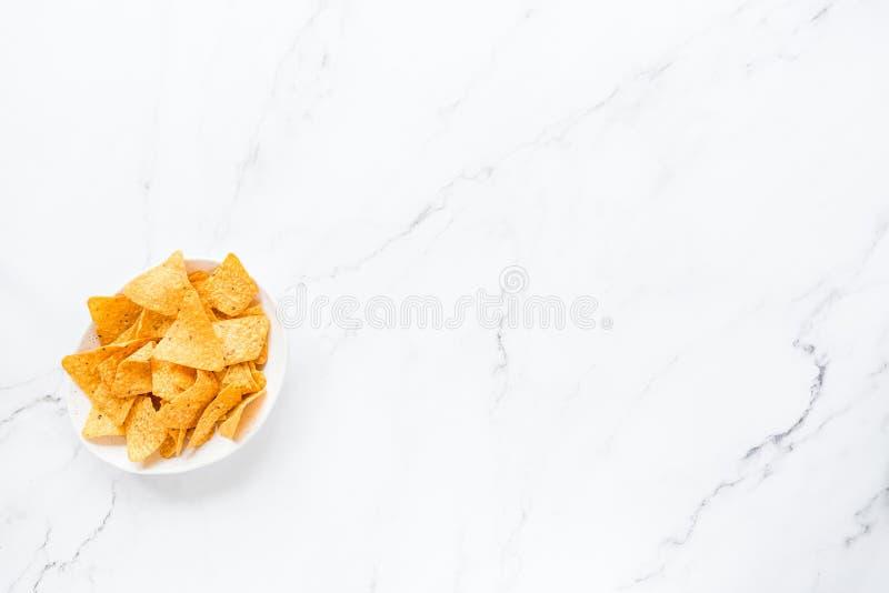 Nachospaanders in witte kom die op marmeren achtergrond liggen Ongezond voedselconcept Vlak leg, hoogste mening, overheadkosten,  royalty-vrije stock fotografie