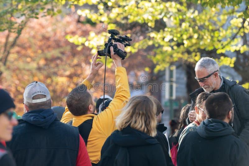 Nachrichtenreporter mit Sony-Videokamera an einer politischen Sammlung lizenzfreies stockfoto