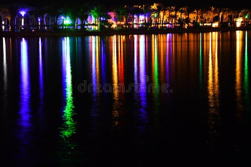 Nacht bliksem en het glanzen strand met kleurrijke lichten en mooie lange bezinning stock fotografie