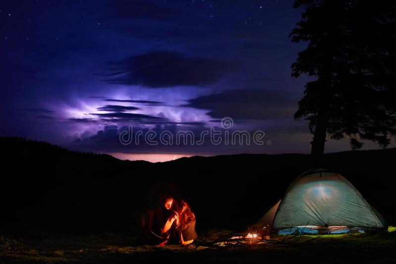 Nacht die in de bergen kamperen De paartoeristen hebben een rust bij een kampvuur dichtbij verlichte tent stock fotografie
