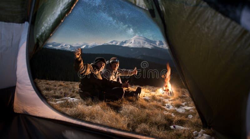 Nacht het kamperen Twee gelukkige toeristen in de bergen bij nacht onder het mooie hoogtepunt van de nachthemel van sterren en me royalty-vrije stock afbeeldingen