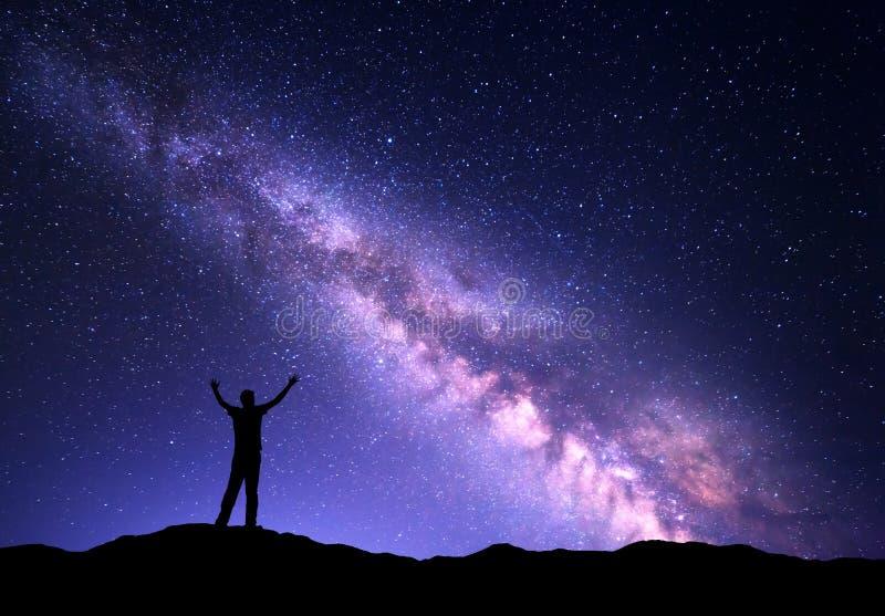 Nacht kleurrijk landschap met purper Melkweg en silhouet van een bevindende sportieve mens met opgeheven op wapens op de berg stock fotografie