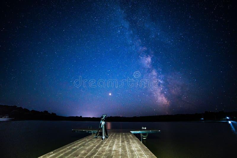 Nacht melkachtige manier met houten pijlercamera op een driepoot stock afbeelding