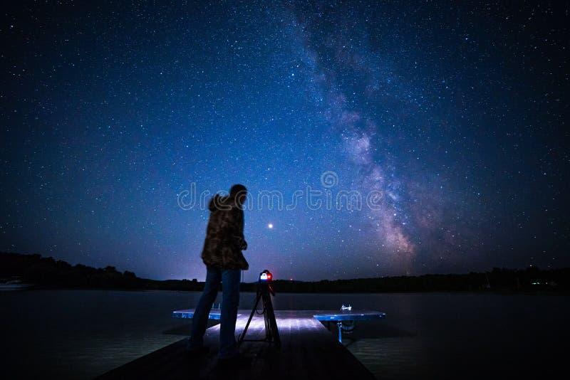 Nacht melkachtige manier met houten pijlercamera op een driepoot stock afbeeldingen