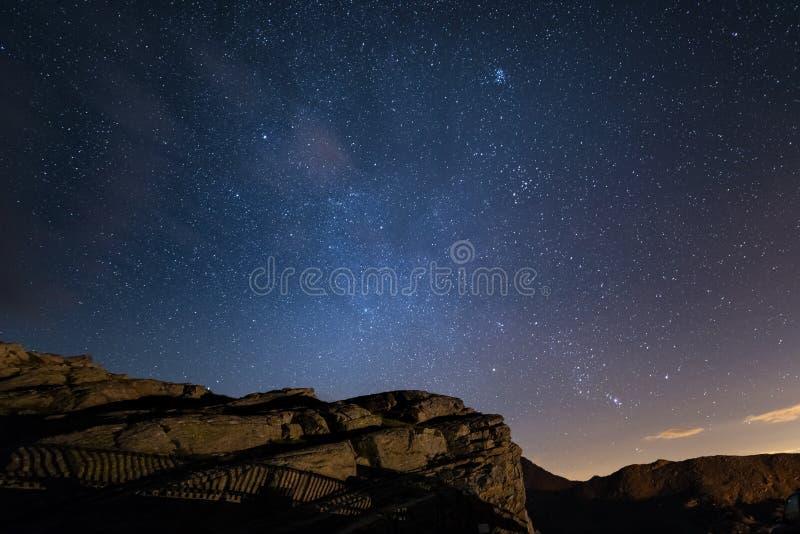 Nacht op de Alpen onder sterrige hemel en de majestueuze rotsachtige klippen op de Italiaanse Alpen, met Orion-constellatie bij d stock foto