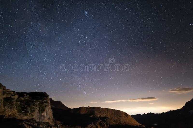 Nacht op de Alpen onder sterrige hemel en de majestueuze rotsachtige klippen op de Italiaanse Alpen, met Orion-constellatie bij d royalty-vrije stock fotografie