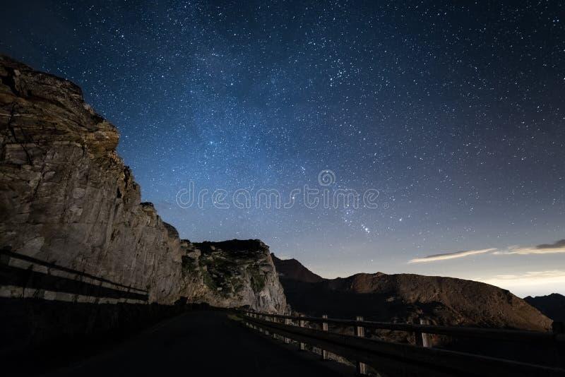 Nacht op de Alpen onder sterrige hemel en de majestueuze rotsachtige klippen op de Italiaanse Alpen, met Orion-constellatie bij d stock foto's