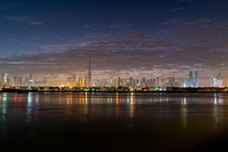 Nacht of schemer in Doubai r Nightly Doubai de stad in Weergeven van overzees aan de kade van Doubai stock foto's