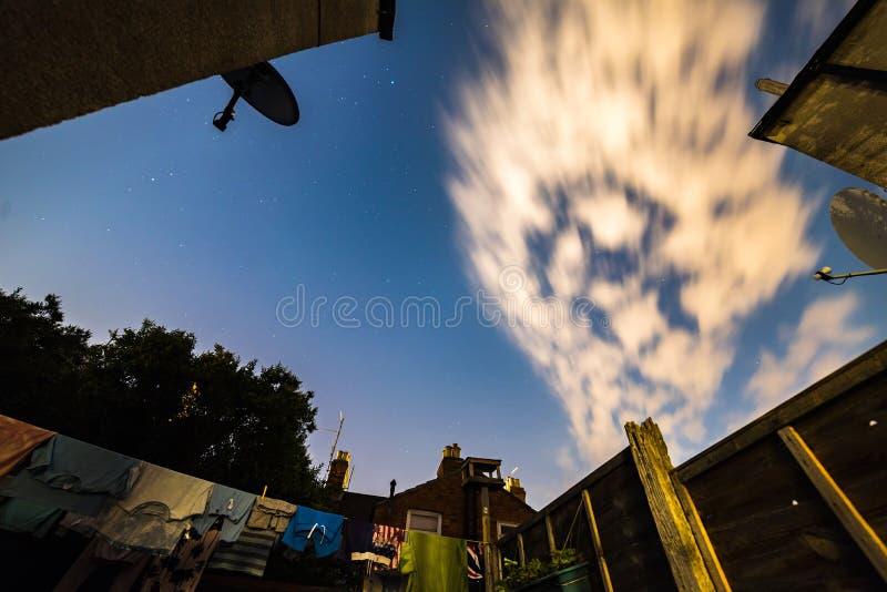 Nacht spielt Himmelansicht vom britischen Hinterhof mit Wäscherei und Satellitenschüsseln um sie die Hauptrolle stockfoto