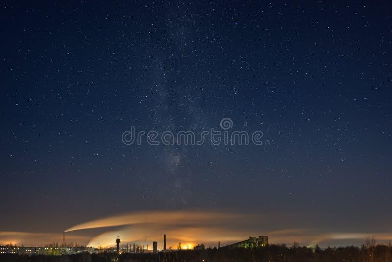 Nacht sterrige hemel met de Melkweg over de industriezone van stock foto's