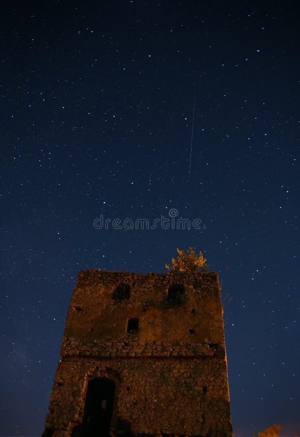 Nacht sterrige hemel over een verlaten steentoren Een dalende ster is zichtbaar Een diepe donkere nacht stock foto's