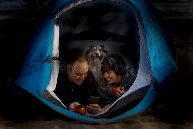 Nacht van mooie copule met hond binnen een tent wordt geschoten die stock afbeelding